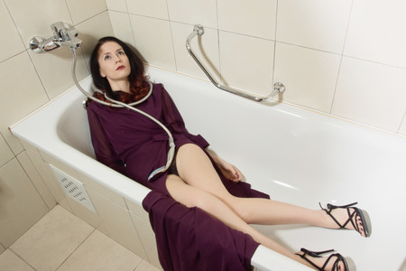 Lifeless beautiful woman lies in a bathtub. She is strangled with a shower hose