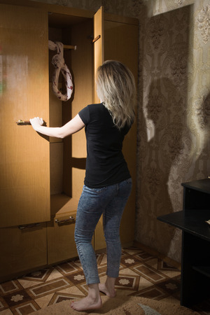 Young woman opening wardrobe with cloth in loop inside Standard-Bild