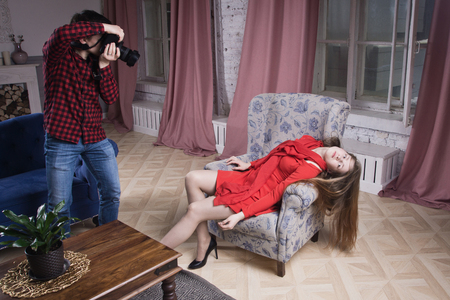 A man photographer takes pictures of a crime scene with a young woman Фото со стока