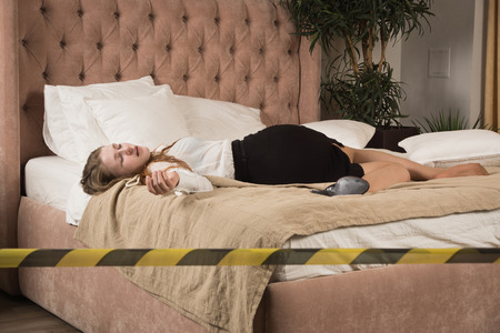 Strangled beautiful business woman in a bedroom. Simulation of the crime scene. Banque d'images - 102876546