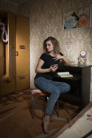 Cyberbulling. A frightened girl gets threats over the phone. Behind her in the closet hangs a loop