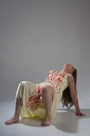 Horror film. A girl in a bloody dress screams in pain  Stock Photo