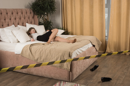 Strangled beautiful business woman in a bedroom. Simulation of the crime scene. Banque d'images - 103154846