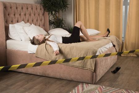 Strangled beautiful business woman in a bedroom. Simulation of the crime scene. Standard-Bild - 103154859