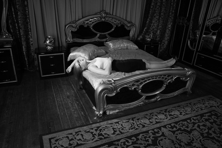 Strangled beautiful business woman in a bedroom. Simulation of the crime scene.