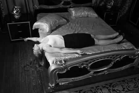 Gewurgde mooie zakenvrouw in een slaapkamer. Simulatie van de plaats delict. Stockfoto