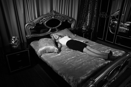 Strangled beautiful business woman in a bedroom. Simulation of the crime scene. Standard-Bild - 110533618