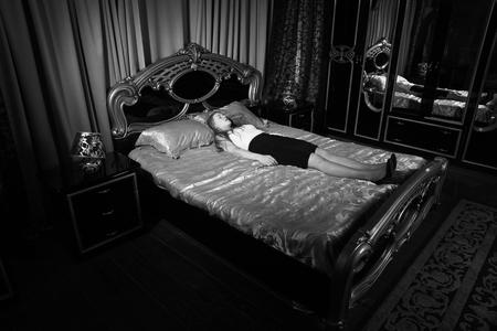 Strangled beautiful business woman in a bedroom. Simulation of the crime scene. Archivio Fotografico - 110542794
