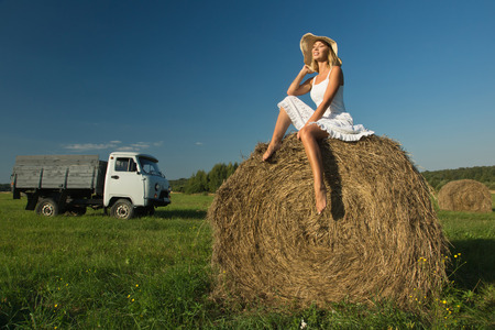 beautiful young girl at a haystack in a summer field