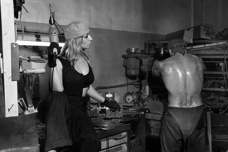 Brutal man and a beautiful woman in a metalwork shop.