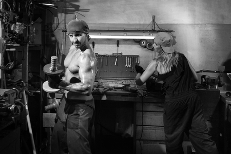 the brutal man in the workshop shakes dumbbells Archivio Fotografico