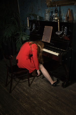 Mujer de belleza incómoda en traje de noche en el piano