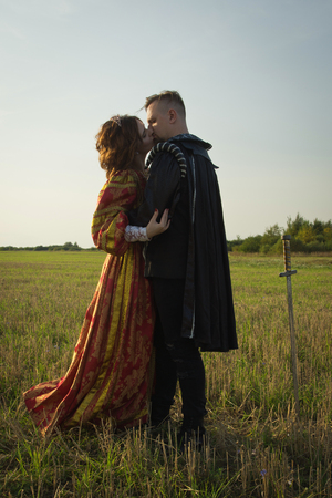 Knight with sword and girl in vintage dress in summer field Stock Photo