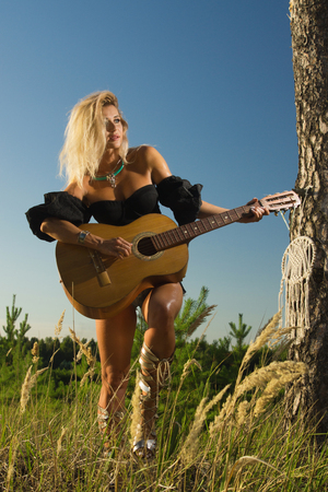 Country girl with guitar in the summer forest