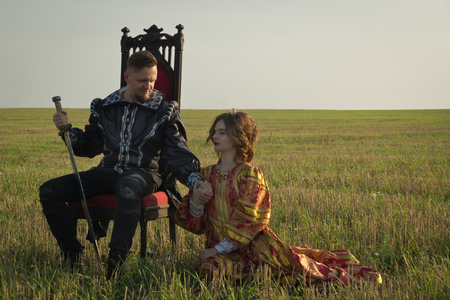 Knight with sword and girl in vintage dress in summer field Archivio Fotografico
