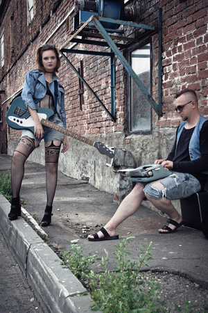 Girl and guy punks on a city street play on guitars