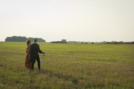 Knight with sword and girl in vintage dress in summer field