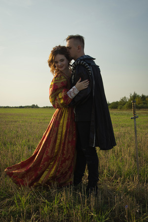 Knight with sword and girl in vintage dress in summer field Reklamní fotografie