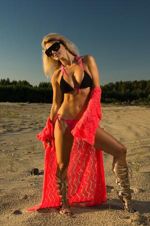 Mujer sexual posando en un desierto arenoso Foto de archivo