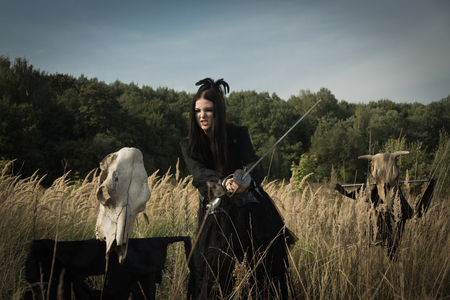 Gothic girl with a sword in her hands next to the skull of a cow on a pole in a summer field