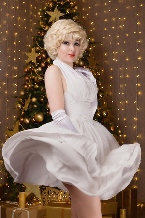 New Year Concept. Pin-up girl with flying white dress in a Christmas room Reklamní fotografie