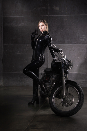 Hit woman. Biker girl in a latex suit with gun in hand