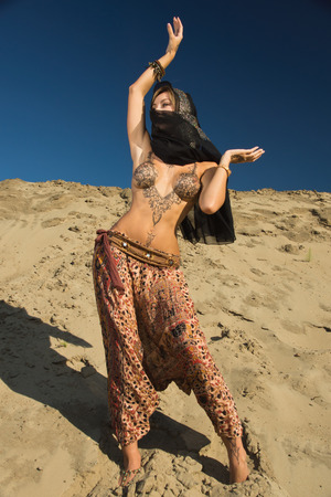 Oriental woman in a sandy desert. Her body is covered with mehendi patterns