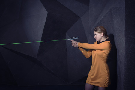 Woman in retro style sci-Fi movie shoots out laser weapons