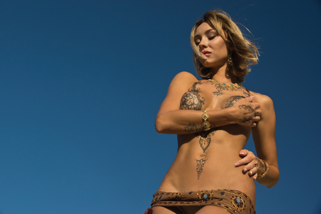 Beautiful woman in a sandy desert. Her body is covered with mehendi patterns