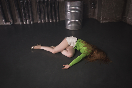 Thriller film. Lifeless unconscious woman lying on a factory floor Stock fotó