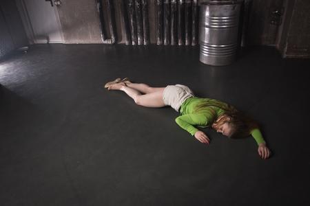 Film thriller. Donna incosciente senza vita sdraiata sul pavimento di una fabbrica