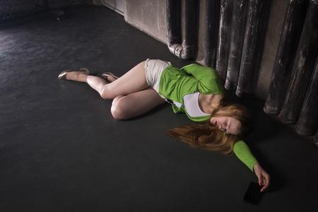 Un film à suspense. Femme inconsciente sans vie allongée sur un sol d'usine