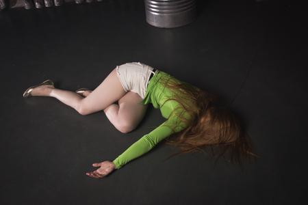 Film thriller. Donna incosciente senza vita sdraiata sul pavimento di una fabbrica Archivio Fotografico