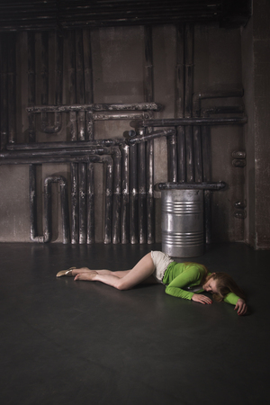 Thriller film. Lifeless unconscious woman lying on a factory floor 写真素材