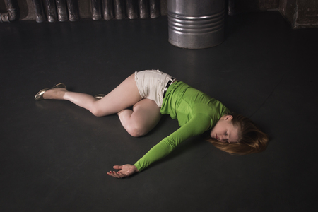Thriller film. Lifeless unconscious woman lying on a factory floor Standard-Bild