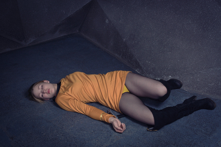 Thriller film. Lifeless unconscious woman lying on a factory floor Standard-Bild