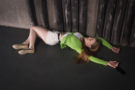 Thriller film. Lifeless unconscious woman lying on a factory floor Banque d'images