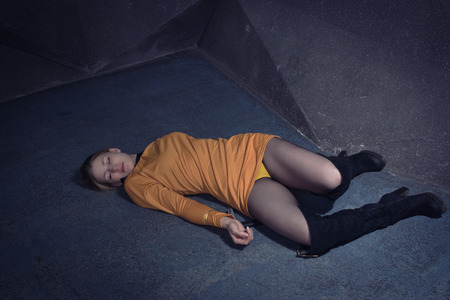 Thriller film. Lifeless unconscious woman lying on a factory floor Imagens