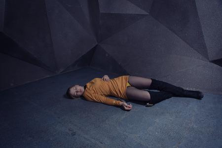 Pelicula de suspenso. Mujer inconsciente sin vida tendida en el piso de una fábrica Foto de archivo