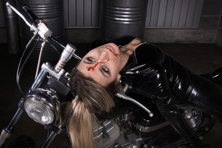 Hit woman. Biker girl in a latex suit killed in gunfire shot in the head