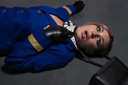 Noir film. Young beautiful flight attendant in uniform being strangled. Not contain any logos or trademark. Archivio Fotografico