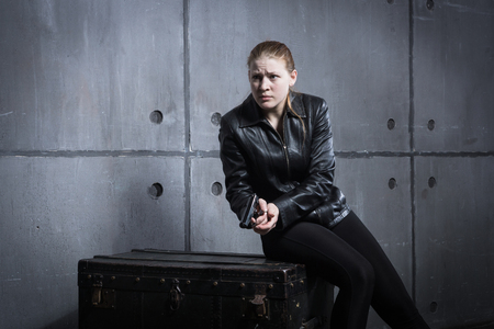 Hit woman. Biker girl in a black suit with gun in hand Stock Photo