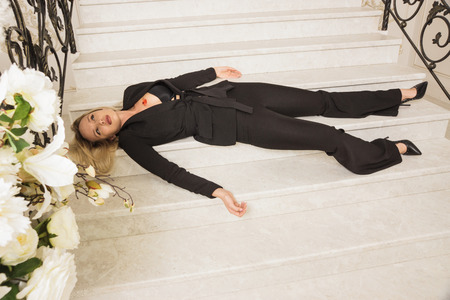 Crime scene. Business woman shot to death on the luxury stairs 免版税图像