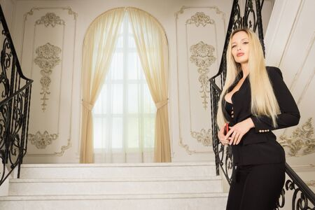 Beautiful young business woman speaks by phone on the stairs in a luxurious interior