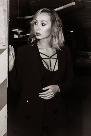 Noir film style woman in a black suit posing in an undergound car park
