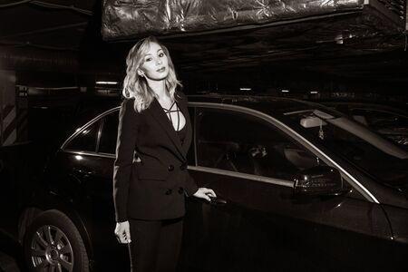 Mujer de estilo de película negra con un traje negro posando en un aparcamiento subterráneo