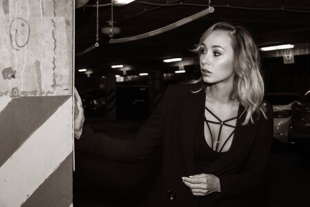 Noir film style woman in a black suit posing in an undergound car park