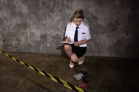 Policewoman criminalist working on a crime scene