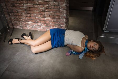Crime scene simulation: dead girl in the handcuffs lying on the floor