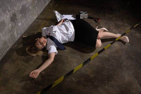 Crime scene imitation. Dead woman police officer lying on a floor